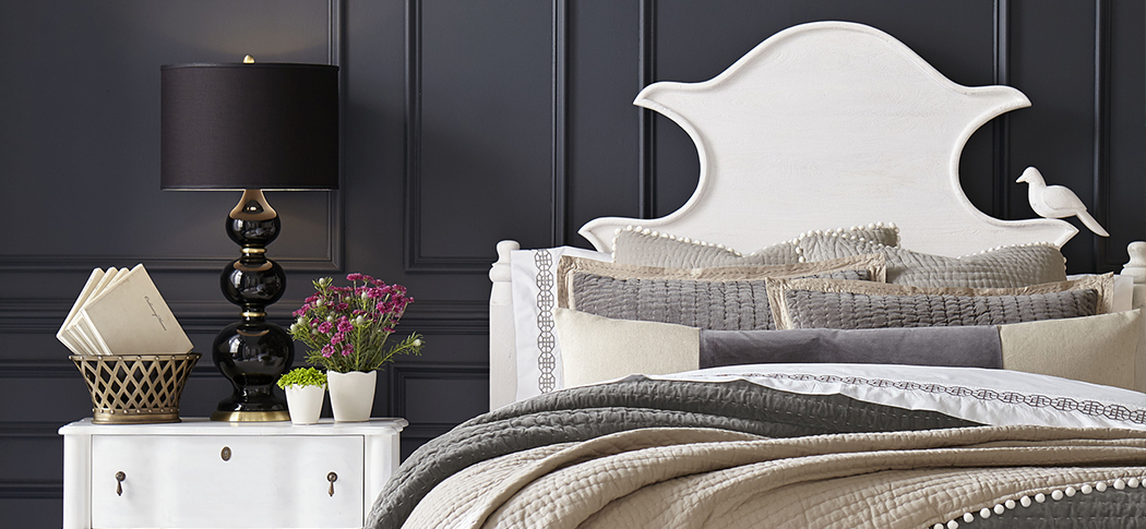 Neutral bedding on white headboard against black wall